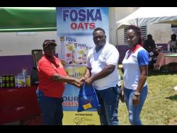 Claudette Anderson receives a gift bag from Jamaica's most successful cricket captain Tamar Lambert, after a bowl-off at the  SDC/ Wray and Nephew National Community T20 Cricket competition at the Dumfries Oval in St James last Sunday, looking on is a representative from Foska Oats.