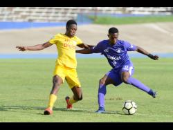 Kingston College's Renaldo Robinson stylishly cuts away from Charlie Smith High School's Kareem Griffiths as 'The Purples' thrash the Jerome Waite- coached team 5-0 in their Manning Cup quarter-final match yesterday.