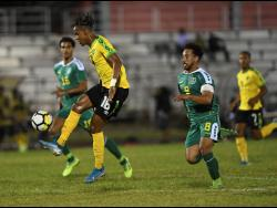 Jamaica's Peter Vassell attempts to control the ball while being pursued by Guyana's Samuel Cox in their Concacaf Nations League encounter at the Montego Bay Sports Complex on November 18, 2019.