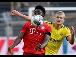 Bayern Munich's Alphonso Davies (left) shields the ball from Dortmund's Erling Haaland during a German Bundesliga match in Dortmund, Germany, yesterday.