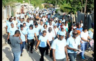 August Town residents march while celebrating peace in their community in 2017.