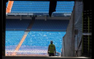 Workers walk into Real Madrid's Santiago Bernabeu Stadium in Madrid, Spain, on Monday, May 25. Spanish league clubs are now allowed to train with groups of up to 14 players as the league stays on track to restart in less than three weeks.