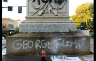In this May 31, 2020 photo, protesters vandalise the  Athens Confederate War Memorial after the main protest ended in downtown Athens, Georgia.