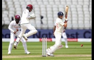 England's captain Joe Root (right) plays a shot during the first day of the third cricket Test match between England and West Indies at Old Trafford in Manchester, England, Friday, July 24, 2020.