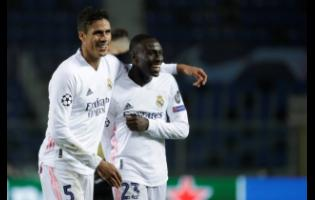 Real Madrid's Ferland Mendy (right) celebrates with Real Madrid's Raphael Varane at the end of the Champions League, round of 16, first-leg match between Atalanta and Real Madrid, at the Gewiss Stadium in Bergamo, yesterday.