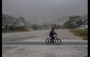 A man rides his bicycle past fields covered with volcanic ash a day after the La Soufriere volcano erupted, in Kingstown, on the eastern Caribbean island of St Vincent and the Grenadines last Saturday.