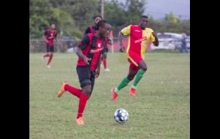 FILE Kemal Malcolm of Arnett Gardens moves away from Humble Lion's Gregory Lewis during their RSPL encounter at Effortville in Clarendon on December 29, 2029.