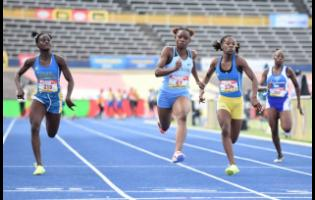 Edwin Allen's Tina Clayton (second left) on her way to victory in the Class Two Girls 100m final, ahead of Hydel High School's Kerrica Hill (second right) and Alana Reid (left). St Catherine High School's Kavel Ritchie, who finished seventh, is also pictured.
