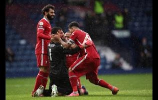 Liverpool's goalkeeper Alisson (black top) celebrates with teammates after scoring his side's second goal during the English Premier League match between West Bromwich Albion and Liverpool at the Hawthorns stadium in West Bromwich, England, yesterday. Liverpool won 2-1.
