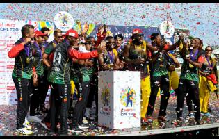 St Kitts & Nevis Patriots players celebrate with the trophy after winning the 2021 Hero Caribbean Premier League finals against St Lucia Kings at Warner Park Sporting Complex yesterday.