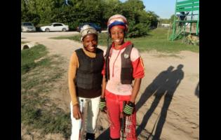 Tamicka Lawrence (right)  stands with fellow female apprentice rider, Abigail Able, at Caymanas Park.