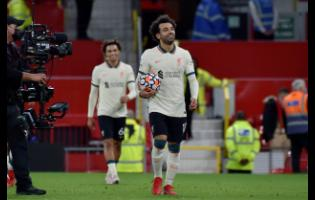 Liverpool's Mohamed Salah leaves the field with the match ball at the end of the English Premier League match between Manchester United and Liverpool at Old Trafford in Manchester, England yesterday. Salah scored three goals in Liverpool's 5-0 win.