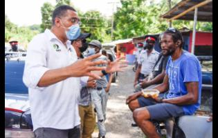 Prime Minister Andrew Holness (left) talks to St Mary resident Rorry Fraser (right) about the importance of being vaccinated against COVID-19.