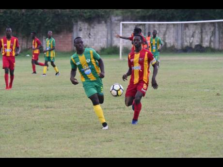 Cornwall College's Solano Birch (right) battles Green Pond High School's Zedford Vacciana in the ISSA/WATA daCosta Cup at Cornwall College football field on September 11, 2019.