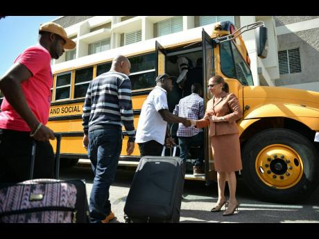 In this 2017 photo, labour minister Shahine Robinson greets some farm workers who are heading off on the overseas employment programme.