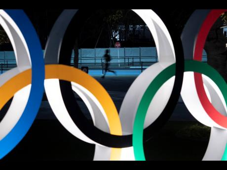 In this March 30, 2020, file photo, a man jogs past the Olympic rings in Tokyo.