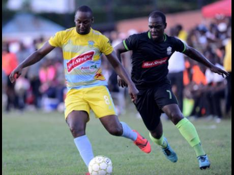 Waterhouse FC's Nicholy Finlayson (left) shields the ball from Molynes United's Devon Hodges during their Red Stripe Premier League match at the Constant Spring Sports Complex on November 3 last year.  Waterhouse won 2-1.