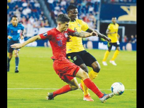 FILE United States midfielder Christian Pulisic (10) kicks the ball past Jamaica midfielder Andre Lewis (4) during the second half of a CONCACAF Gold Cup semi-final match Wednesday, July 3, 2019.